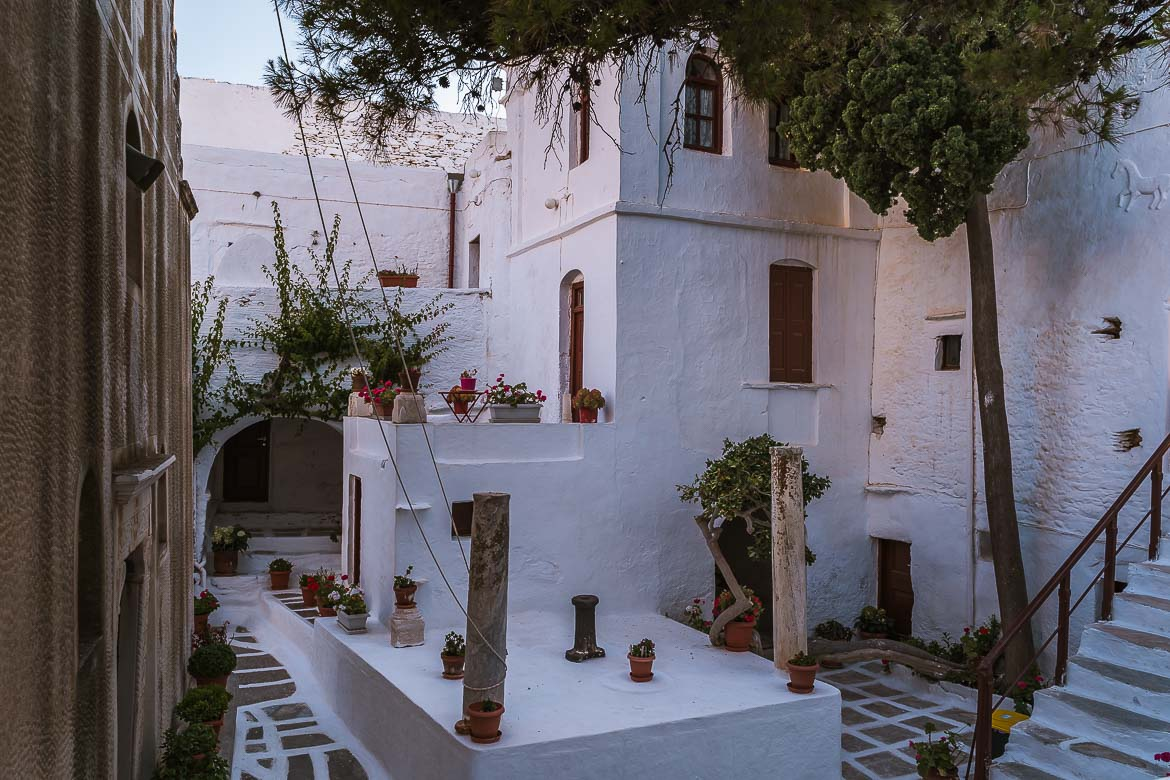 This image shows the internal courtyard of the monastery of Taxiarches. It's whitewashed, filled with lovely flower pots and trees.