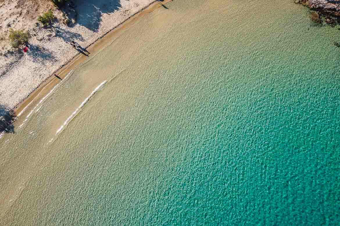 This image shows the transparent turquoise waters of Psili Ammos beach shot from a drone. Spending time on the island's beautiful beaches is one of the best things to do in Serifos.
