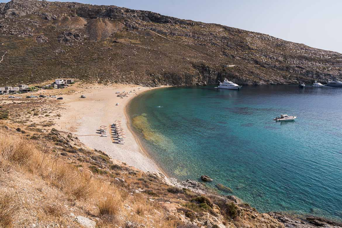 This image shows Vagia beach. There's a long sandy beach with emerald waters and a few yachts anchored near the shore.