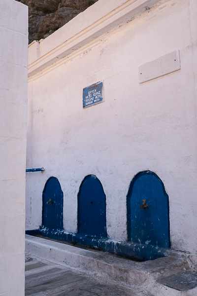 This image shows the Kefalovryso spring in Kato Chora. It's a whitewashed building with blue details and three water taps.