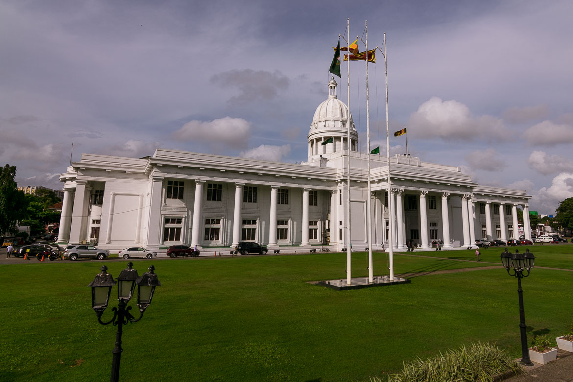 This photo shows the Town Hall of Colombo. It is a white colonial building. Fresh green lawn stretches around the building.