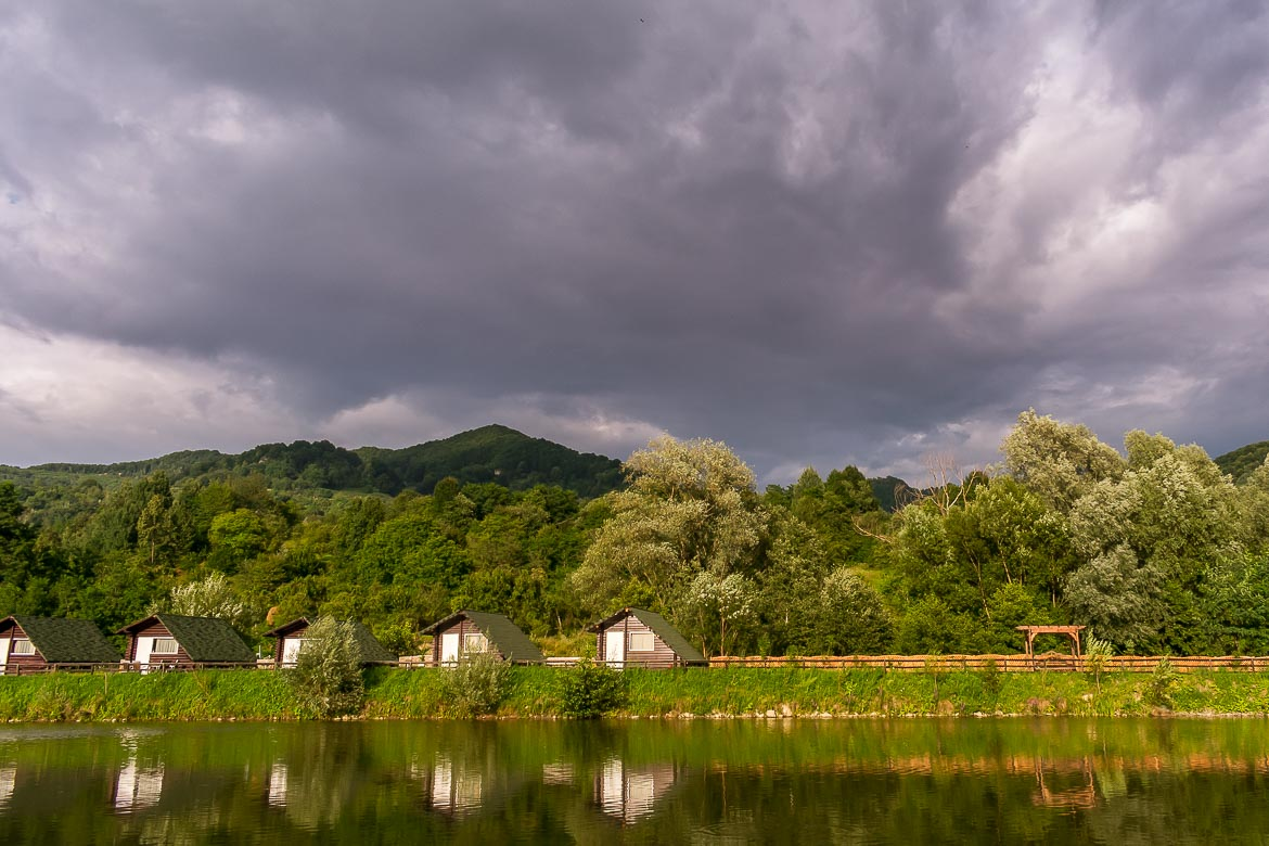 This photo shows a line of wooden huts in front of a lake at Casa Lazaroiu hotel. Green scenery below a grey early evening sky.