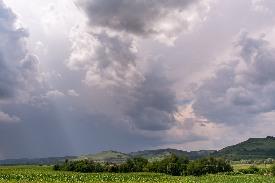 This photo was taken while we drove somewhere in Romania. It is an image of serene, green countryside and a cloudy yet magnificent sky.