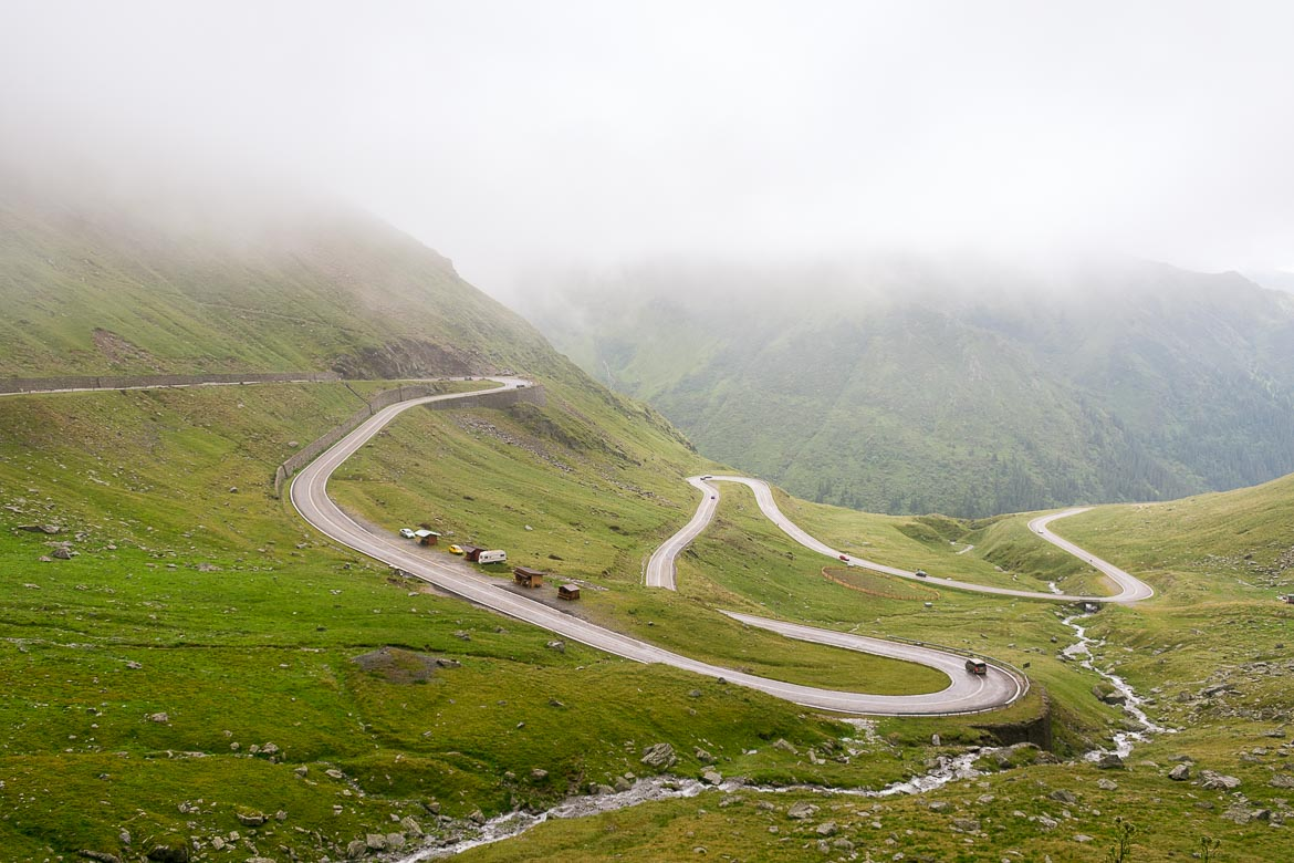 This photo shows the hairpins of the Transfagarasan on a green setting with the fog looming over the mountain tops.