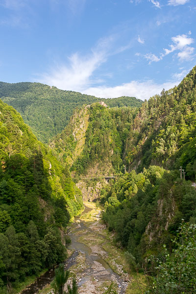 This photo show Poenari Castle in the distance, the way we saw it during our Transfagarasan road trip. Poenari is built atop a cliff surrounded by mountains and streams. A really dramatic scenery.
