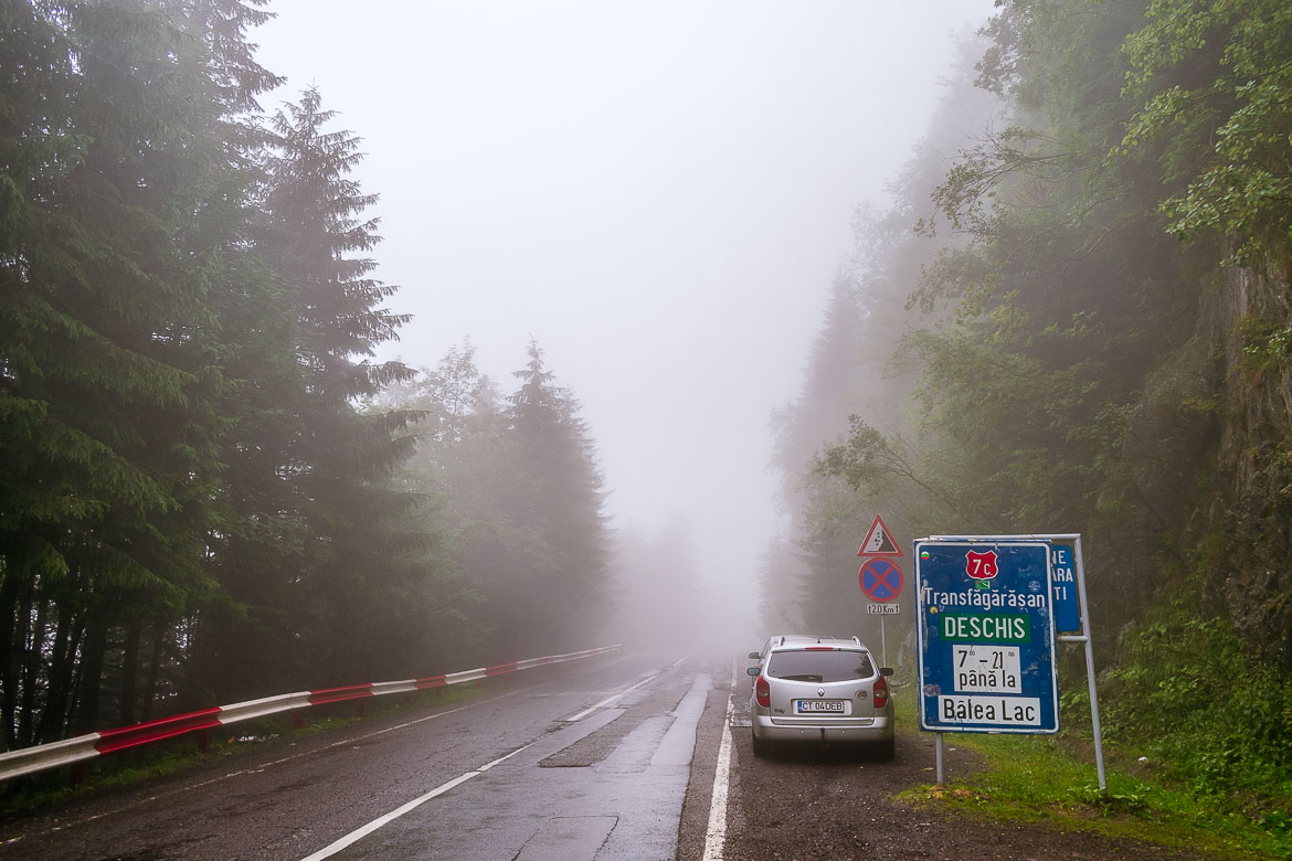 This photo shows the road sign near Balea Waterfall which indicates whether the Transfagarasan Highway is open from that point onwards or not. In this case, it reads deschis, which means open. Everything is covered in fog in the distance.