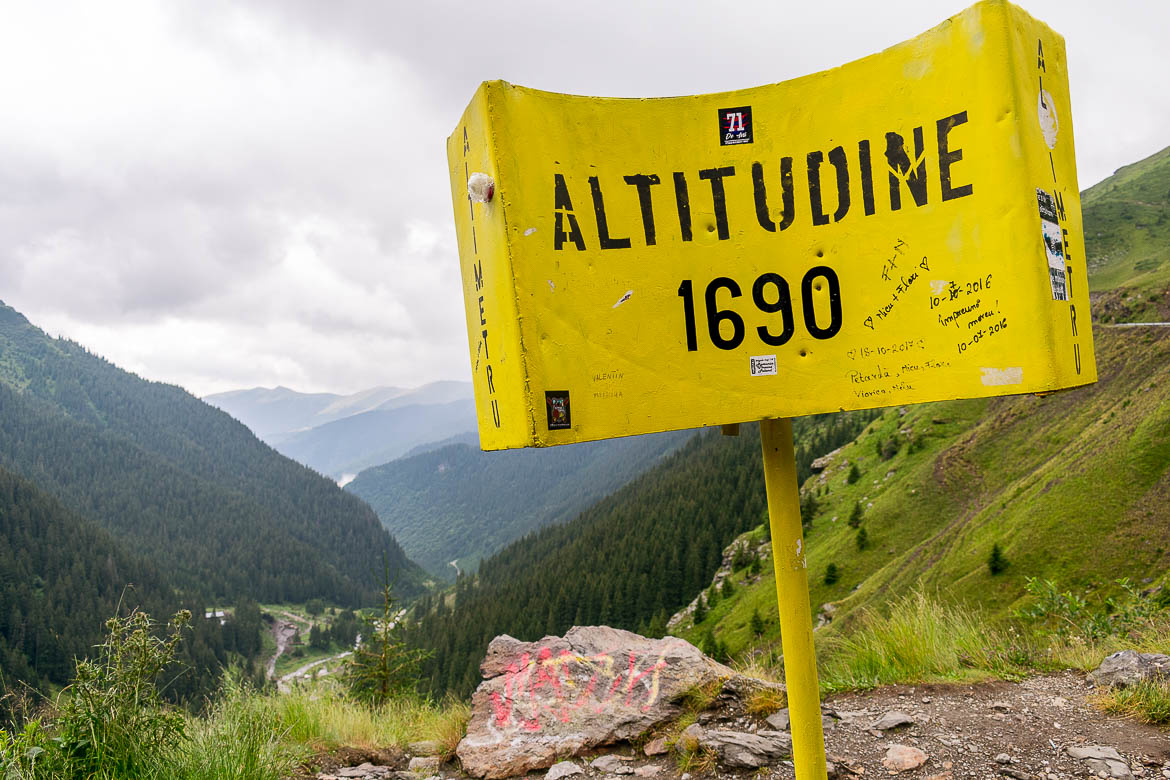 This is a road sign along the Transfagarasan. It is yellow and it reads: Altitudine 1690. It shows the altitude of the specific spot on the road.