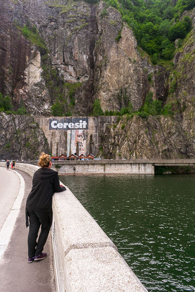 This is a photo of Maria standing on the Vidraru Dam, an essential stop on our Transfagarasan road trip. She has her back turned to the camera and she is looking at the lake.