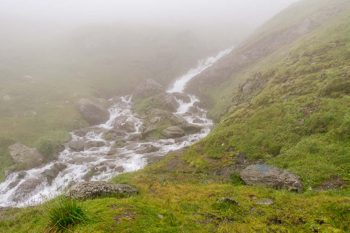 This photo shows a beautiful waterfall at the side of the road. There is fog everywhere.