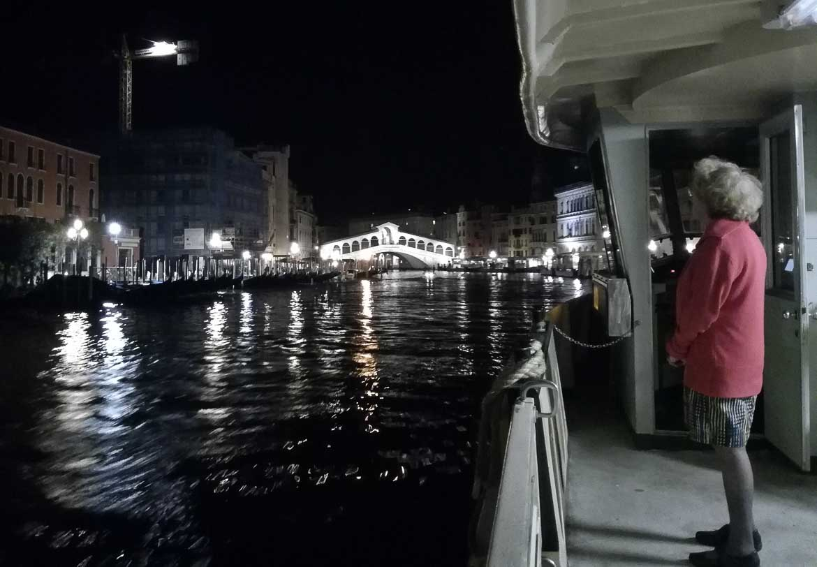 This photo shows the Rialto bridge in Venice as seen from a vaporetto at night. What to do in Venice: our complete guide to La Serenissima. Venice Italy.