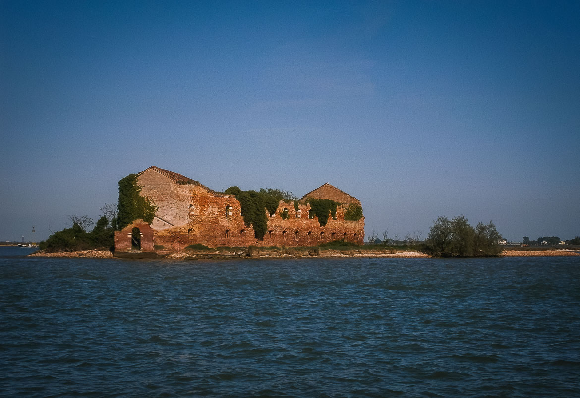 This photo shows a deserted island with a ruined building at the Venetian Lagoon, Veneto Italy. Venice islands, the perfect Venice day trip.