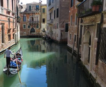 This photo shows a gondola in a quiet canal in Venice.