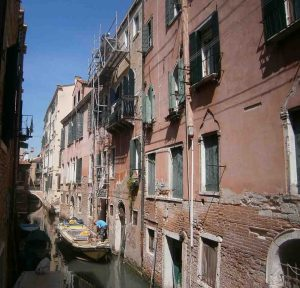 This photo shows builders on a boat in a canal in Venice carrying out construction works on a beautiful old building. What to do in Venice: our complete guide to la serenissima.