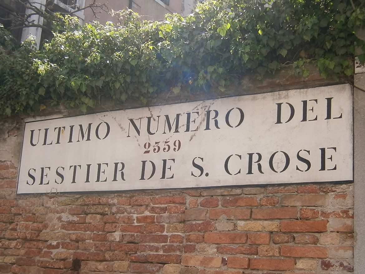 """This photo shows a street sign in Venice Italy, which reads """"Ultimo numero del Sestier de S. Crose"""". What to do in Venice: our complete guide to La Serenissima."""