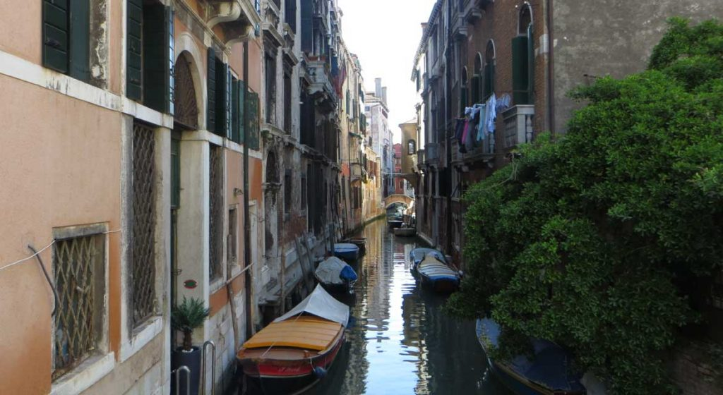 """This photo shows a typical canal in Venice where residents """"park"""" their boats outside their houses. What to do in Venice: our complete guide to La Serenissima."""