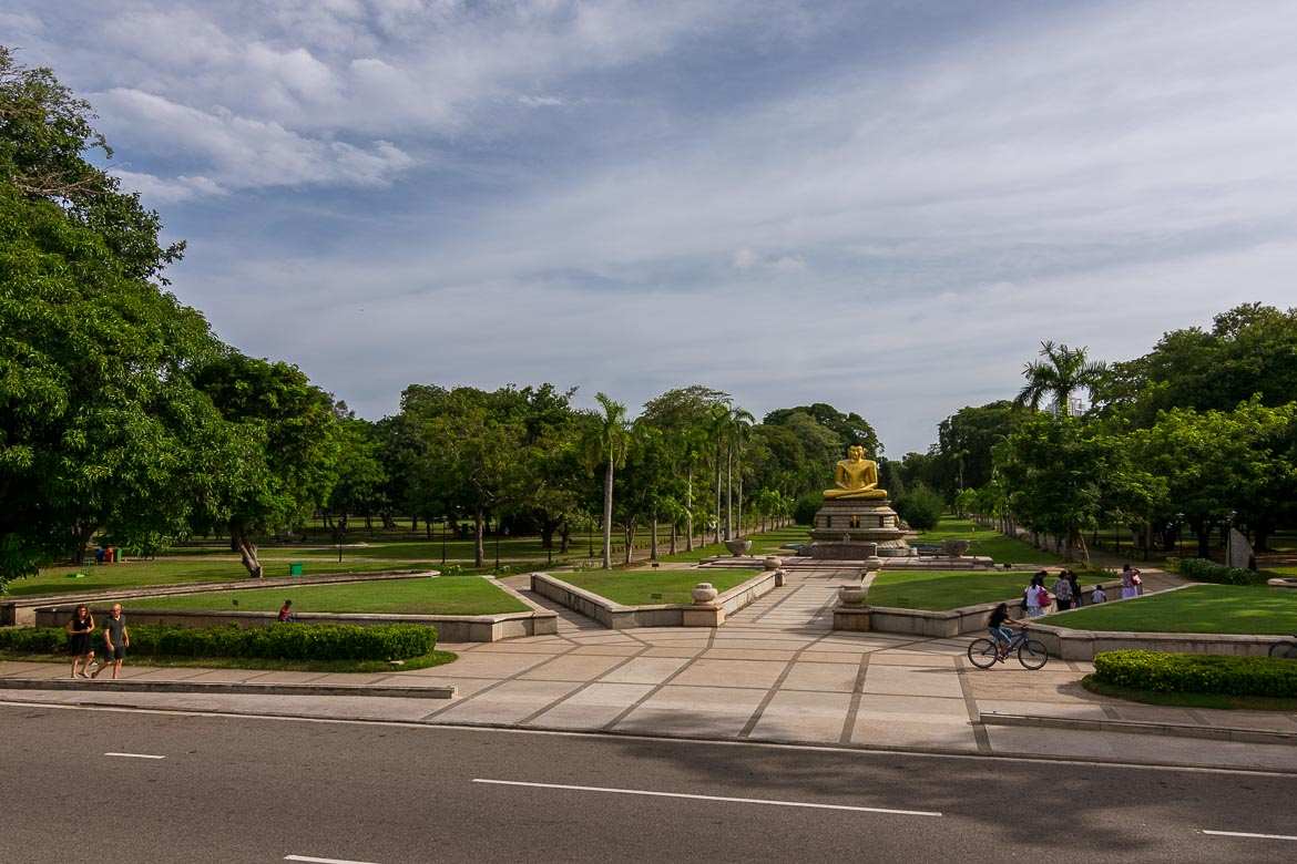 This is a panoramic shot of Viharamahadevi park. We can see a large golden Buddha statue at the park's entrance.