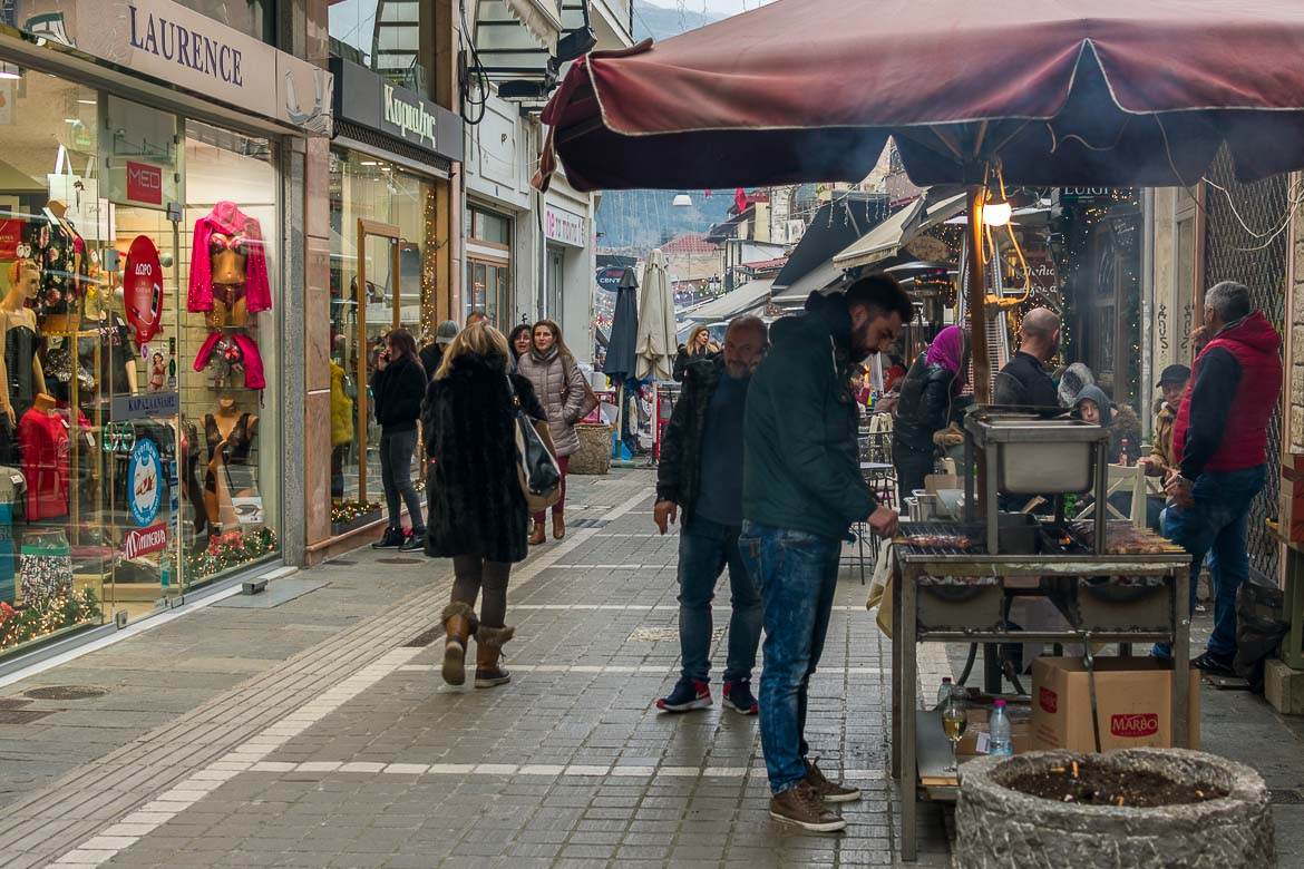 This photo shows a main pedestrianised street in Ioannina. There are many people walking around. Also, there are makeshift barbecues at the side of the srteet.