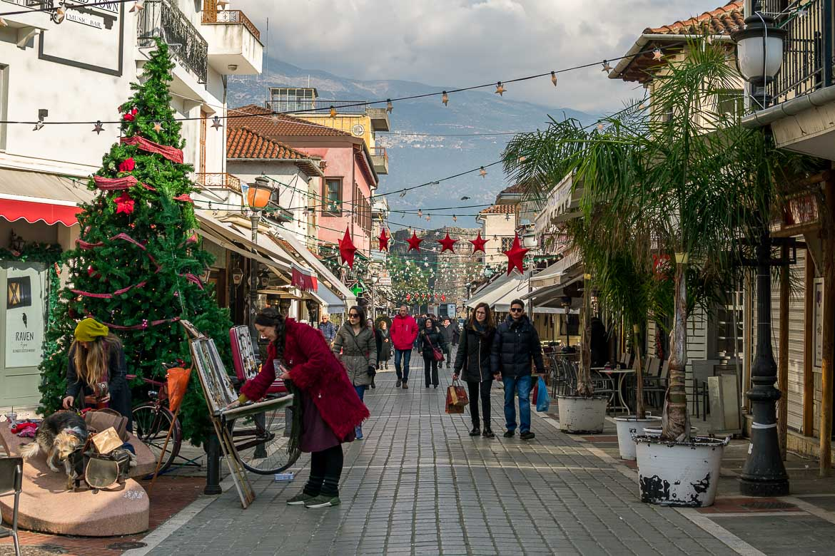 This photo shows one of the main pedestrinised streets in the city of Ioannina. There are Christmas decorations and many people.
