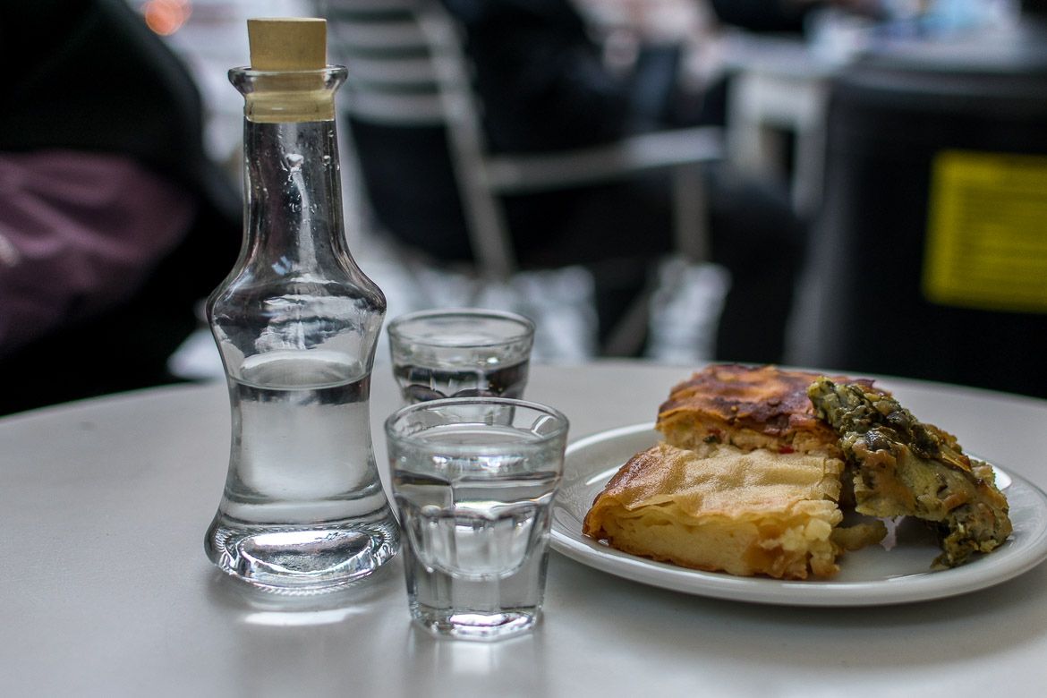 This is a close up of local raki and a small meze dish. There is handmade pie. Ioannina is famous for pies.