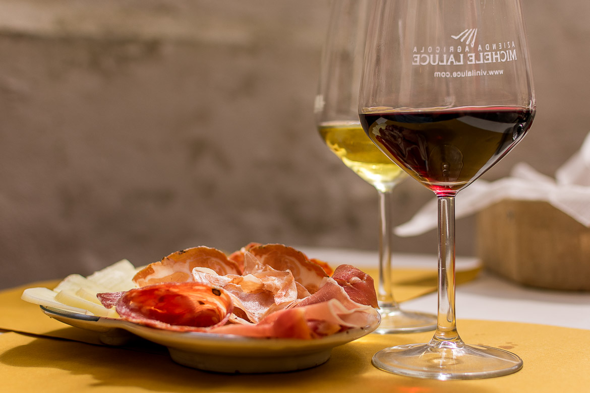 This photo shows two glasses of Aglianico wine (one red, one white) with a platter of cold cuts and cheese at Vicolo Cieco in Matera.