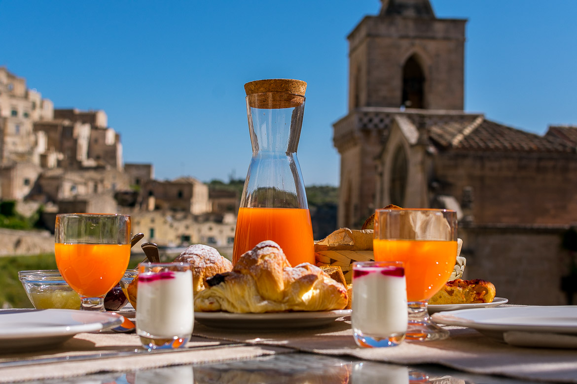This image shows the breakfast at La Corte dei Pastori. There is orange juice, croissants and yoghurt. In the background, San Pietro Caveoso and the Sassi.