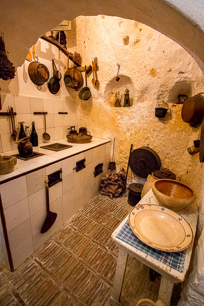 This image shows the interior of the kitchen at La Casa Grotta di Vico Solitario. The kitchen is tiny and all cooking utensils hang from the walls. There are shelves carved on the cave wall.