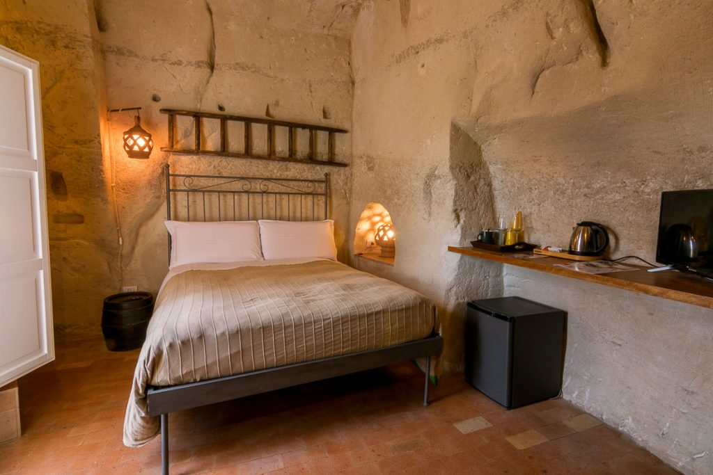 This image shows one of the cave rooms at La Corte dei Pastori. There is a bed with a bronze frame and the room is carved in the rock. There is a byzantine cross carved on the cave wall.