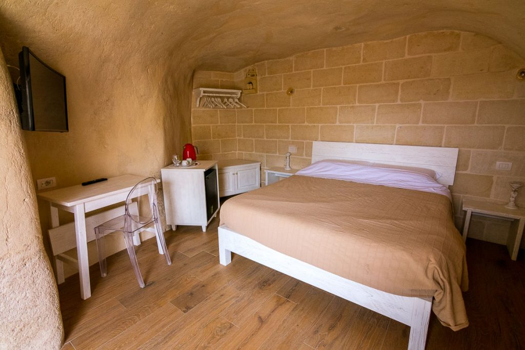 This image shows one of the cave rooms at La Corte dei Pastori. There is a white bed and other pieces of white furniture. The room is carved in the rock.
