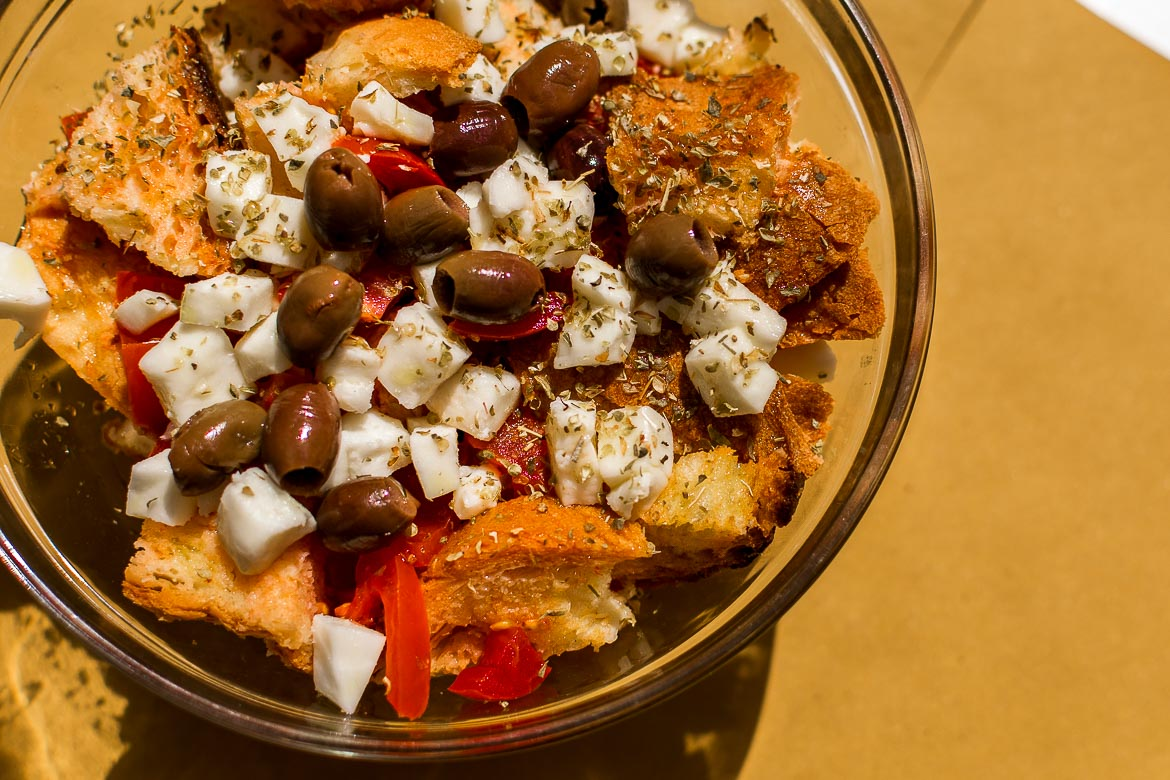 This image shows a typical dish of Matera, the cialledda materana salad. It is made of tomatoes, local cheese, olives and stale bread.