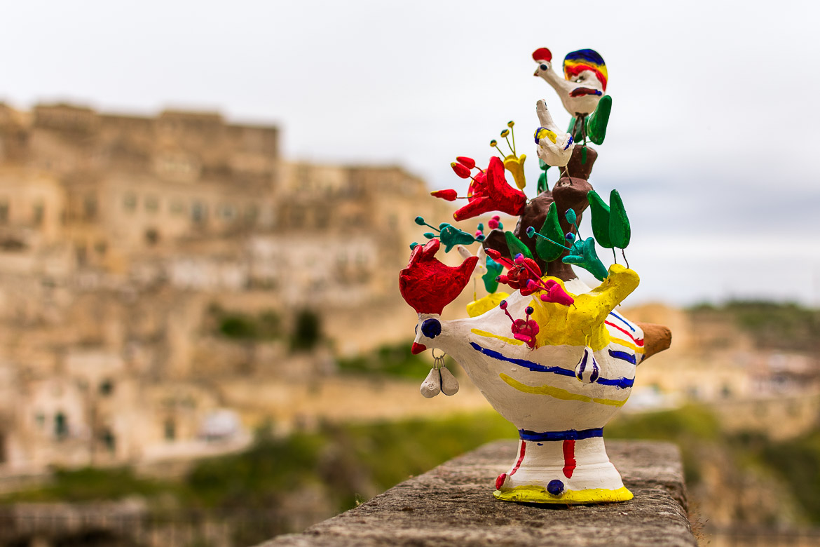 This image shows a very large and elaborate cucu'. It is painted in many vivid colours. In the background, the spectacular views to the Sassi of Matera.