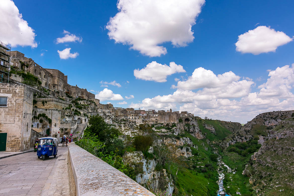 This is a photo of Madonna delle Virtù Street. There is a blue Piaggio Ape on the street.