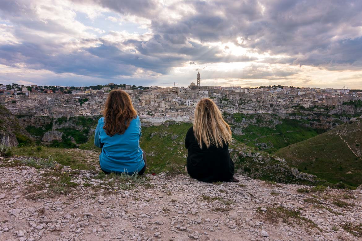 This is an image of Katerina and Maria with their backs turned to the camera. They are sitting on a roch at Murgia Timone admiring the view of Matera across the ravine. The sky is dramatic with the rays of the sun mingling with grey clouds. It is almost sunset.