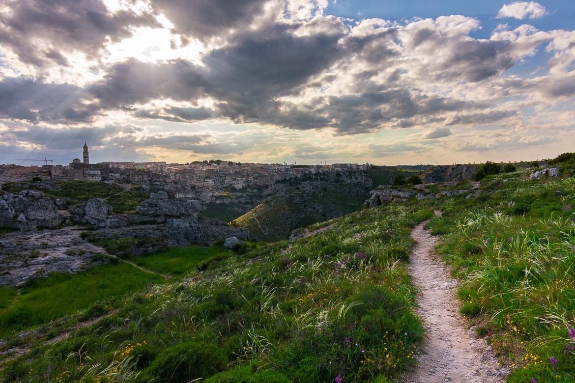 This image shows a hiking path at Murgia Timone. In the background, Matera looks splendid under the cloudy sunset sky.