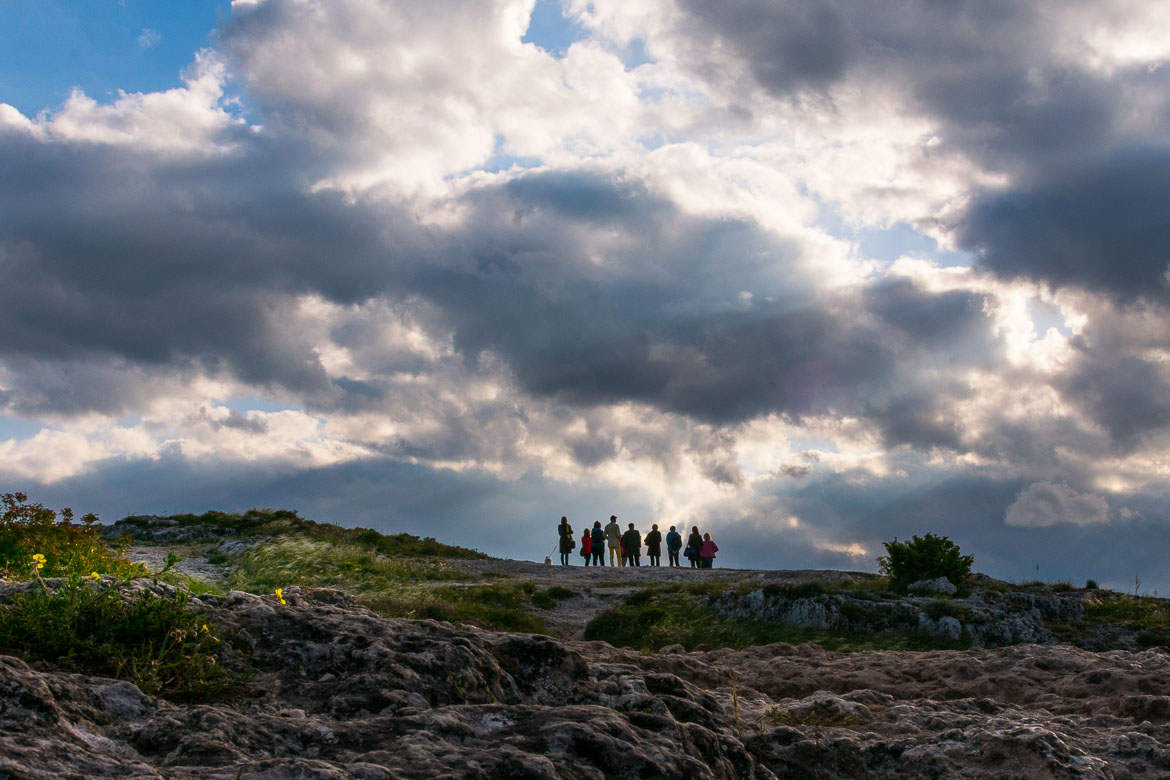 This image shows the silhouettes of a group of people standing on a rock at Murgia Timone under a dramatic cloudy sky.
