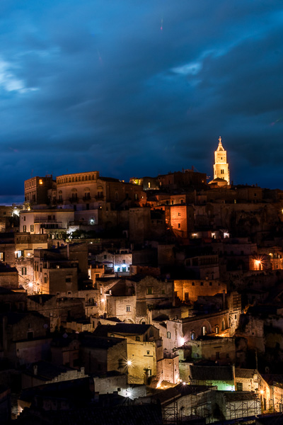 This is a night shot of Matera. The duomo dominates the evening sky while the other buildings are all dimly lit.