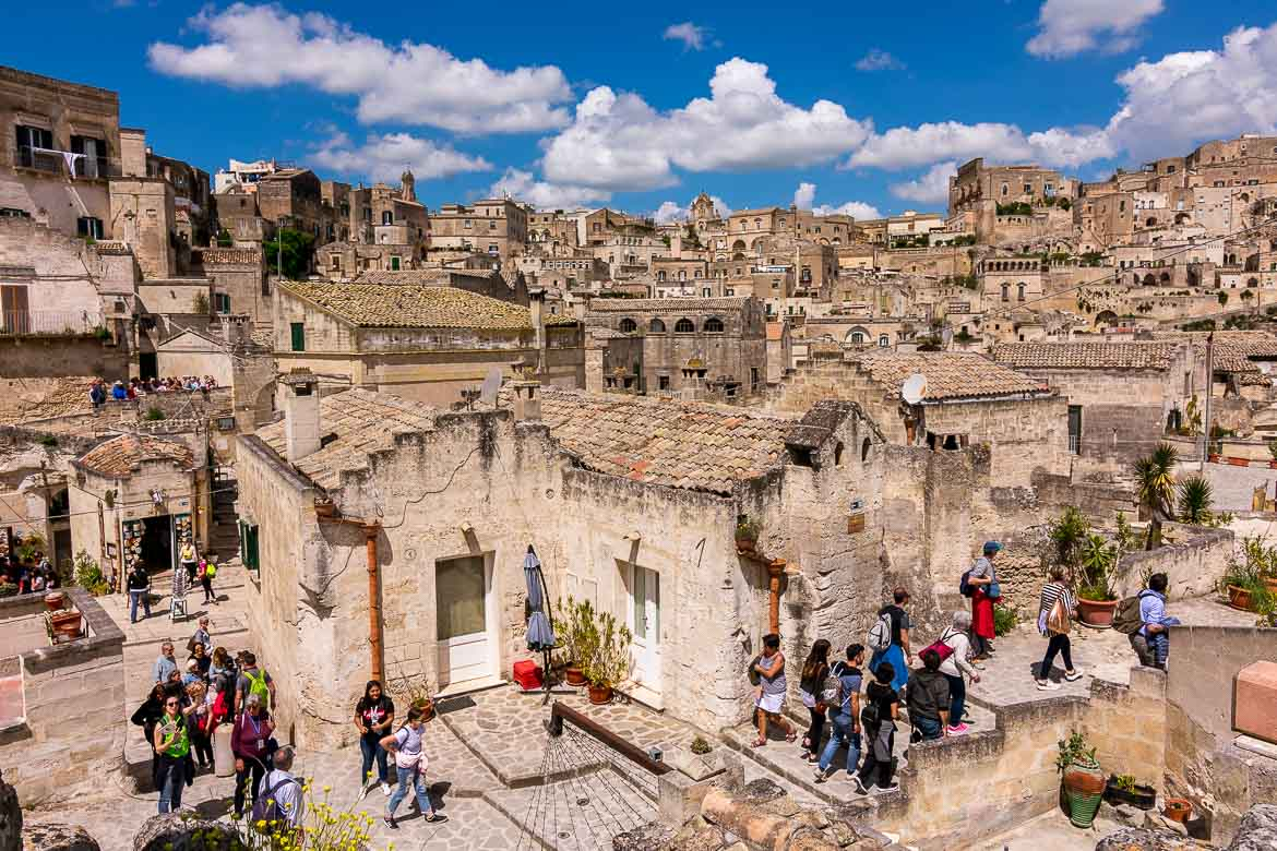 This image shows many people walking along the narrow streets of the Sassi in Matera.