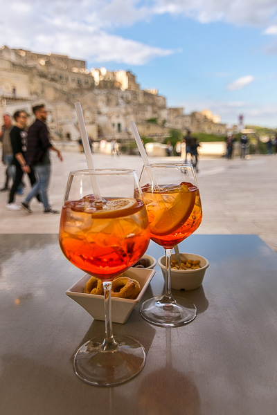 This photo shows 2 Aperol Spritz cocktails on a table. In the background, the spectacular view to the Sassi of Matera.