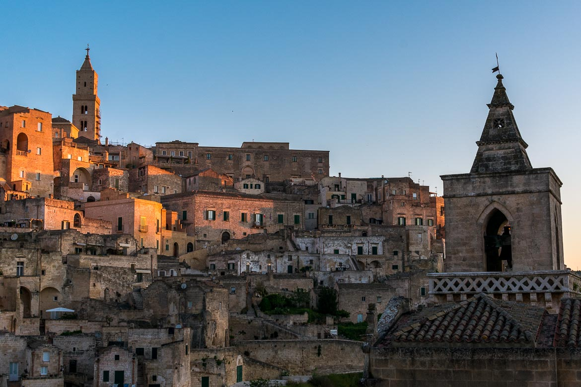 This image shows Matera at dawn. The red colour of the sunrise reflects on the Duomo and other buildings.