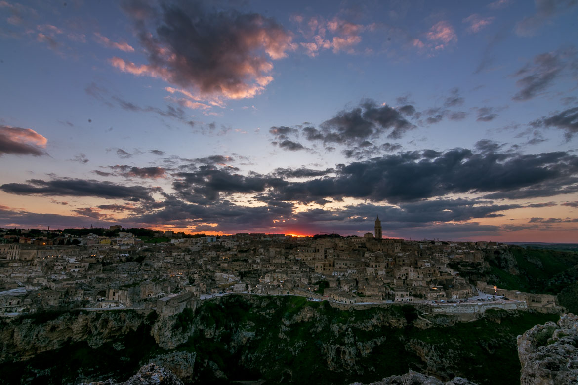 This image shows a spectacular sunset over Matera as seen from the Belvedere at Murgia Timone. It is a panoramic view of Matera and the sky is dramatic with all hues of red and yellow alongside grey and black clouds.