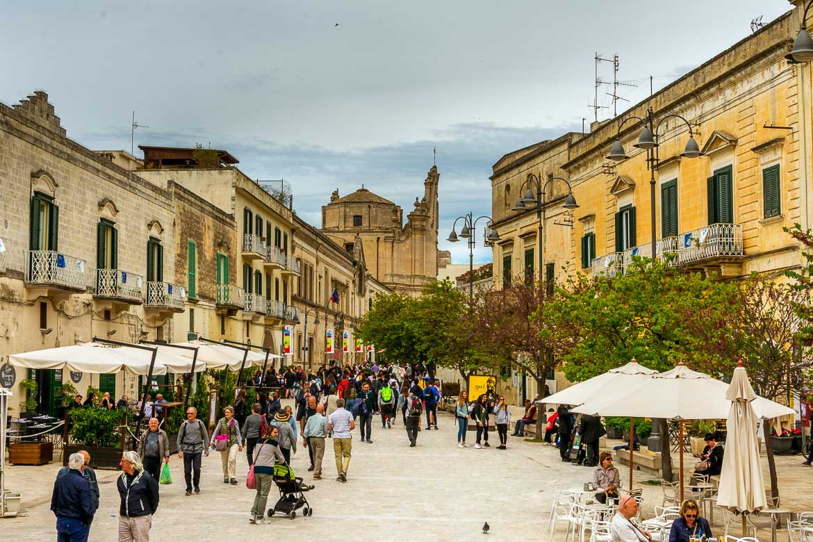 This image shows Via Ridola in Matera. The pedestrianised street is lined with beautiful old buildings. There are people walking along the street or sitting at the outdoor cafes.