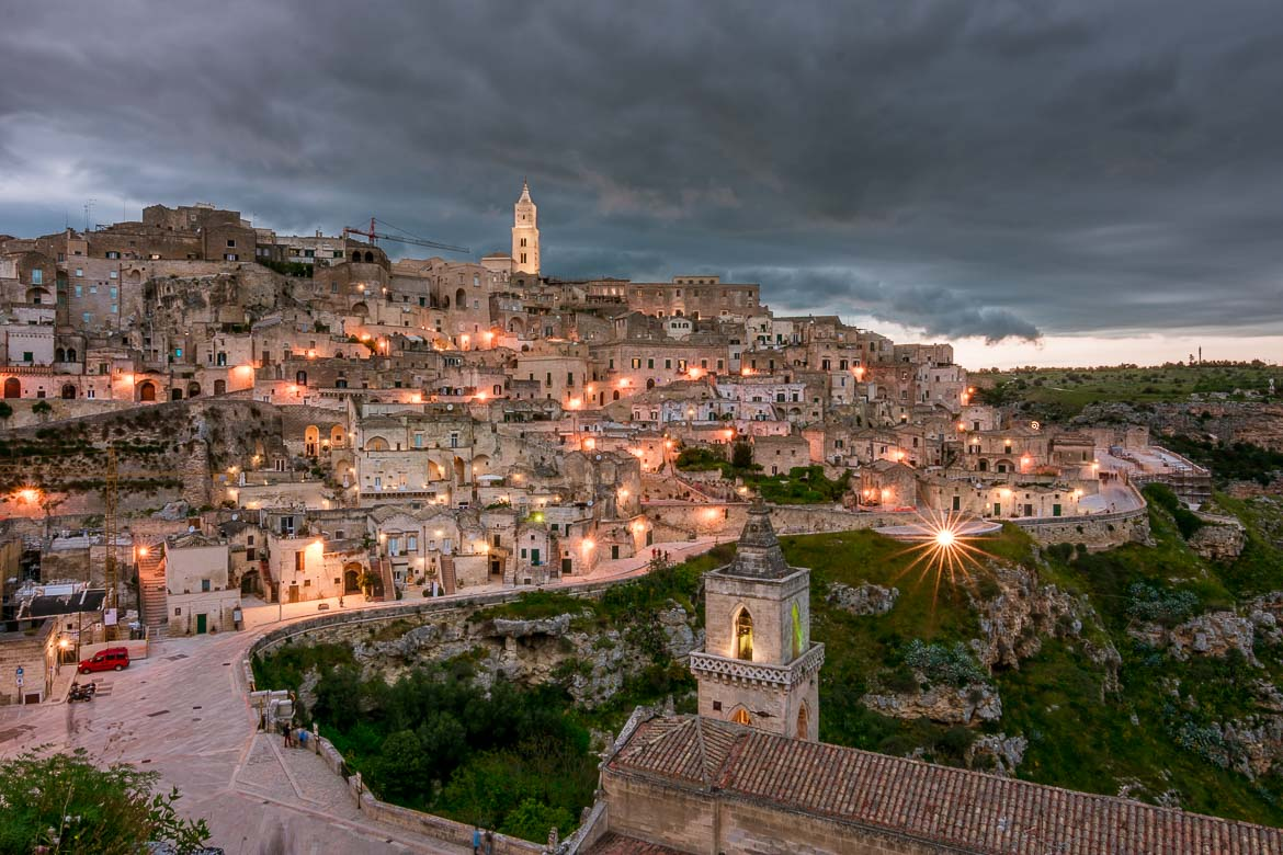 This photo shows a spectacular view of Matera at dusk. The street lights create a nativity scene effect.