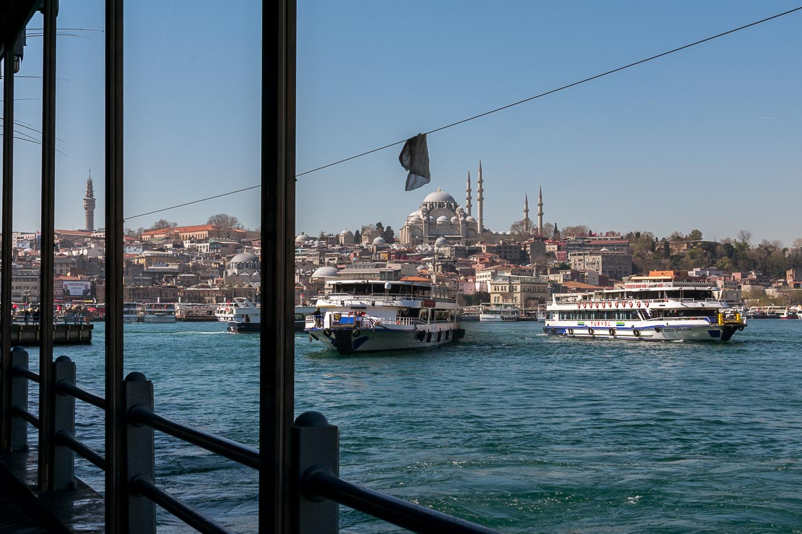 This image was taken from Galata Bridge in Istanbul and shows the sea with many ferries and a mosque in the distance.