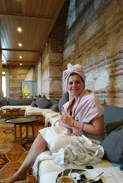 This image shows Katerina wrapped in towels and resting on a comfortable sofa after her hamam experience.
