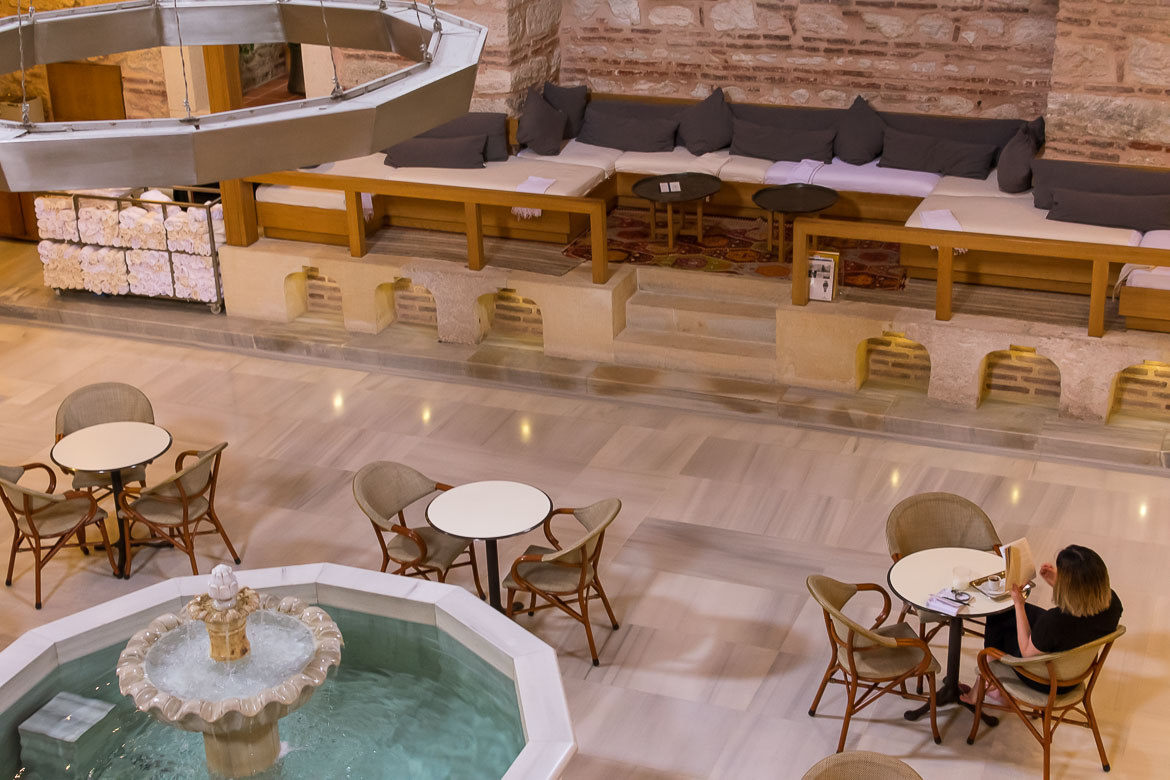 This image shows the lounge area at Kilic Ali Pasa Hamami from above. There is a white marble fountain in the centre of the room. There are tables and chairs around the fountain and huge comfortable sofas along the room's walls.