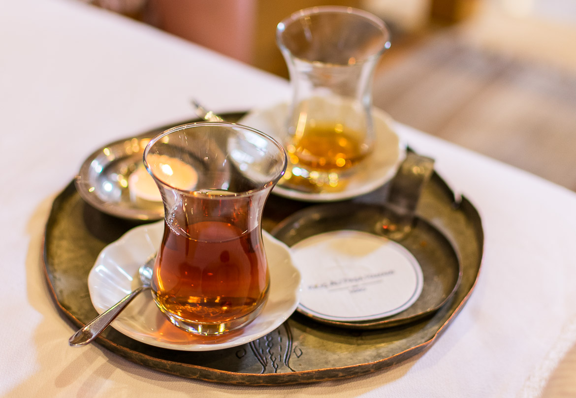 This image shows a tray with two glasses of Turkish tea and a candle at Kilic Ali Pasa hamami in Istanbul.