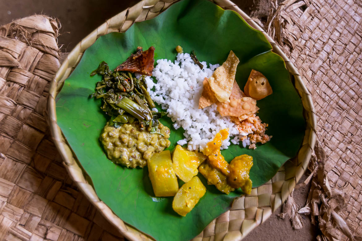 This photo shows food served inside a plate made of cane or coconut leaves.