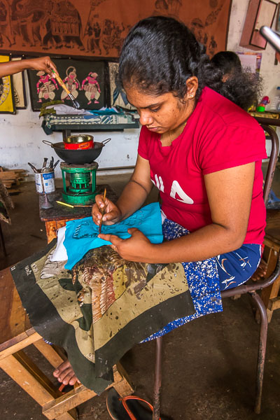 This photo shows a Sri Lankan girl dying a batik garment in her workshop.