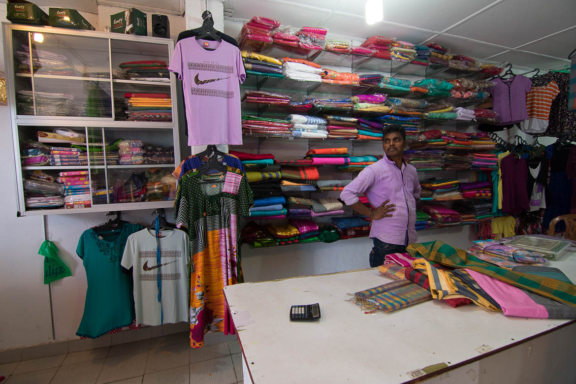 This photo was shot inside a clothes and fabrics shop in Trincomalee Sri Lanka. There are shelves filled with sareed and T-shirts on hangers. The salesman poses for the camera.