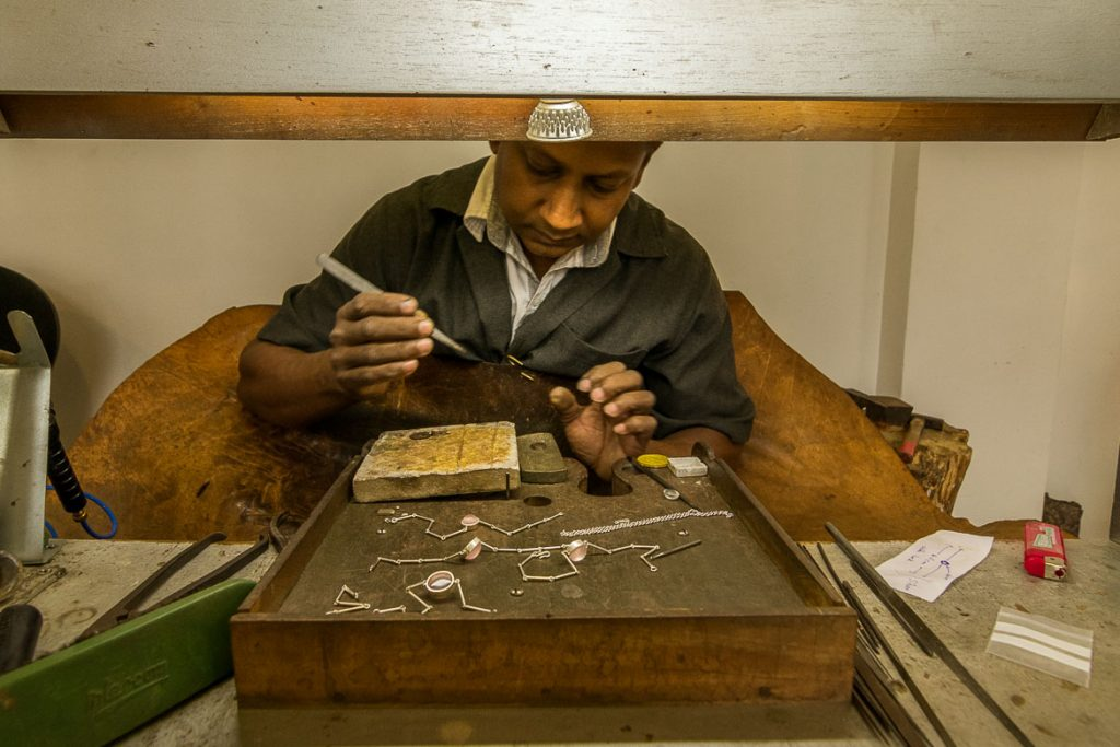 This photo shows a man making jewellery with gemstones at Isini in Kandy.