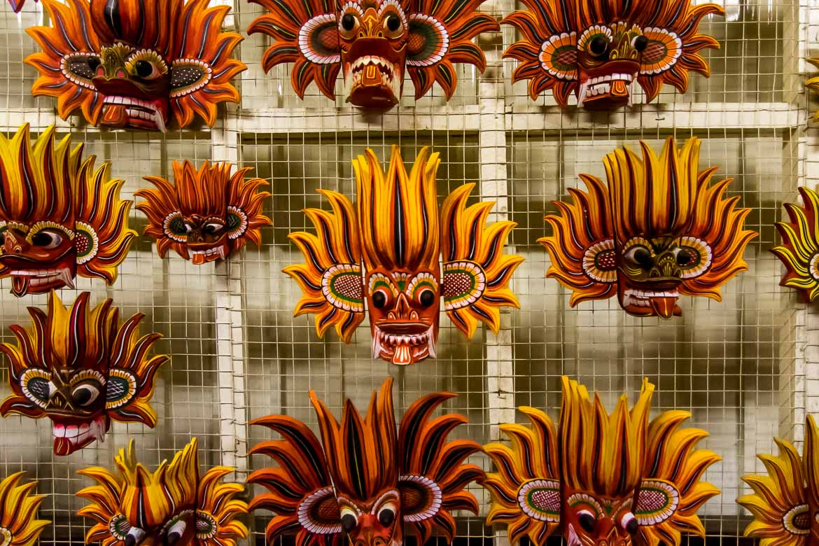 This photo shows many wooden masks in yellow and red colours hanging on the wall of a shop in Kandy.